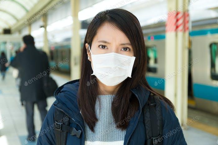 Woman wearing face mask at train platform