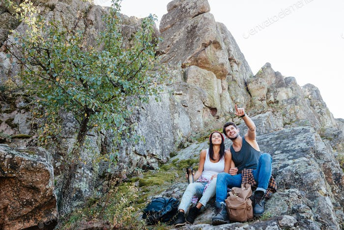 Young active couple enjoying view from top of a mountain