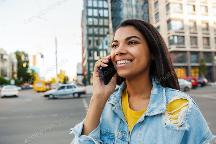 Cheerful young woman making a phone call outdoors