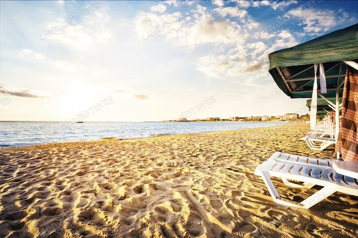 Sandy beach with the sunbeds