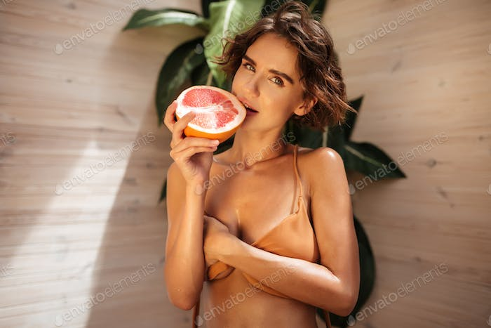 Portrait of beautiful girl in beige bikini thoughtfully looking in camera with half of grapefruit