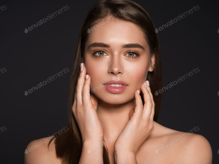 Woman beauty face hands touching close up over dark background