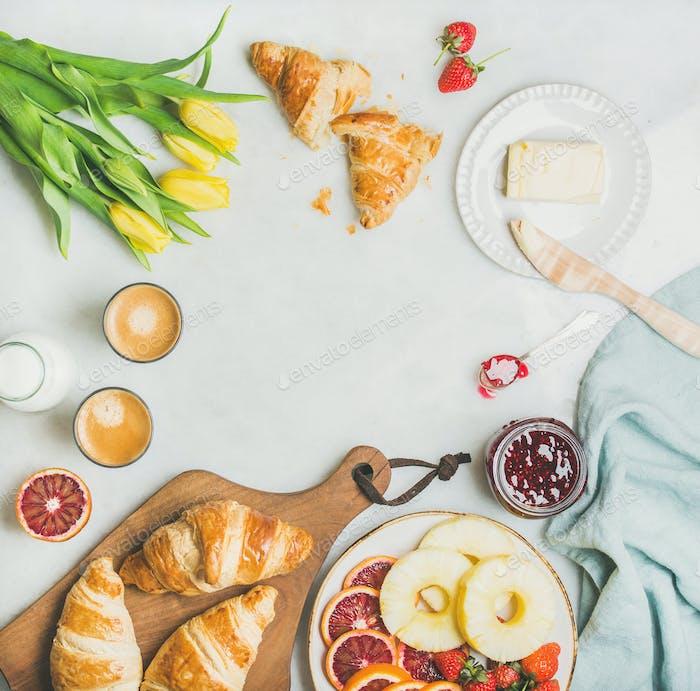 Frühstückstisch mit Kaffee, Milch, Pasrties, Marmelade und gelben Tulpen