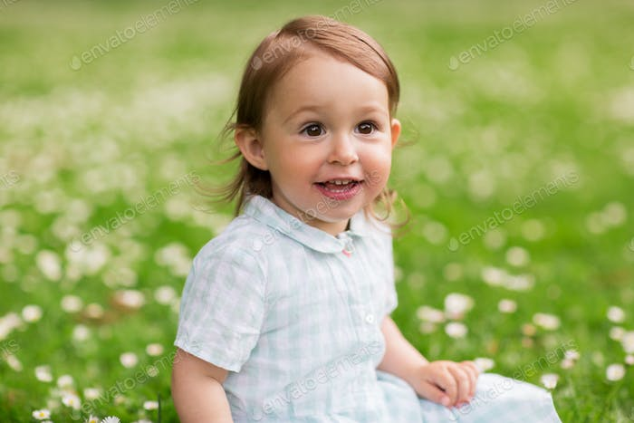 happy baby girl on green summer field