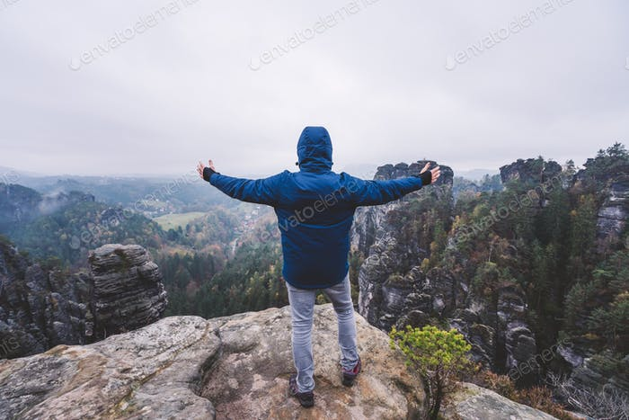 Hiker in outdoor clothing raised hands on the top of a mountain and enjoying view of cliffs ridge