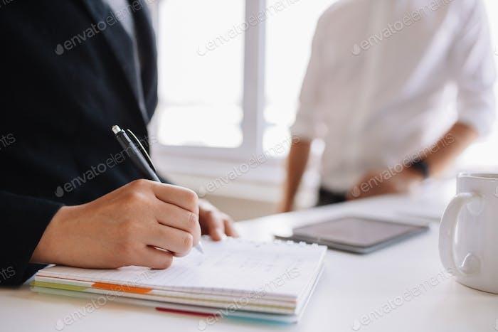 Mujer Encantador notas con colega masculino en el Fondo