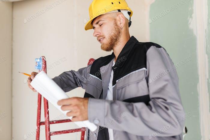 Ingenieur in Arbeitskleidung und gelbe Hardhat träumig Blick auf