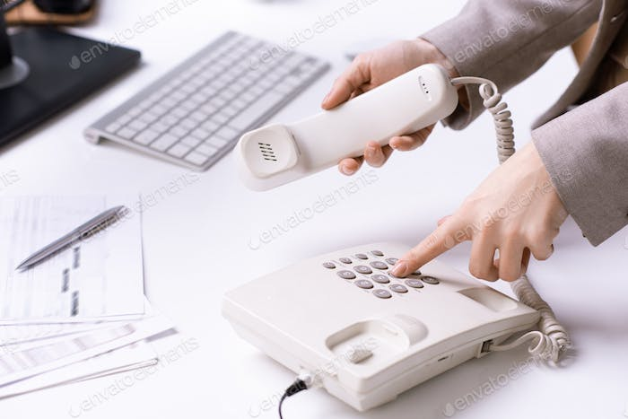 Hands of young office secretary dialing phone number and holding receiver