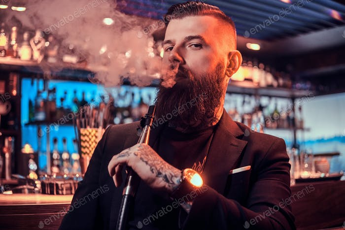 Portrait of tattooed bearded man which is smoking hookah, making nice vapour