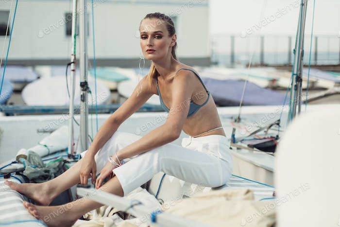 Young beautiful woman in swimsuit top and white trousers wearing