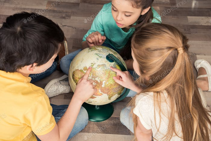 high angle view of boy and girls searching countries on globe