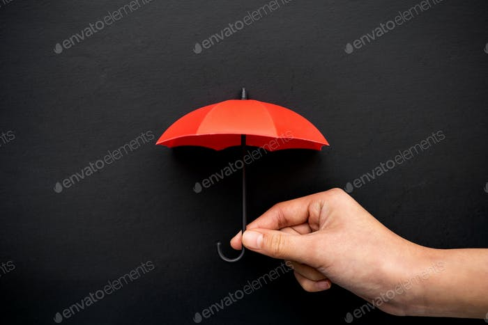 Hand hold a small red umbrella for protection concept