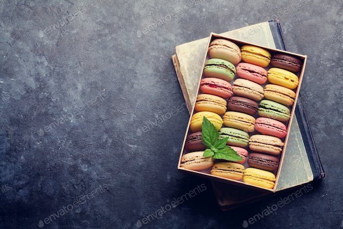 Colorful macaroons in a box over book