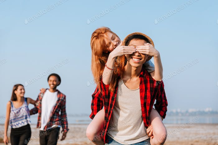 Happy woman covered eyes of her boyfriend by hands outdoors