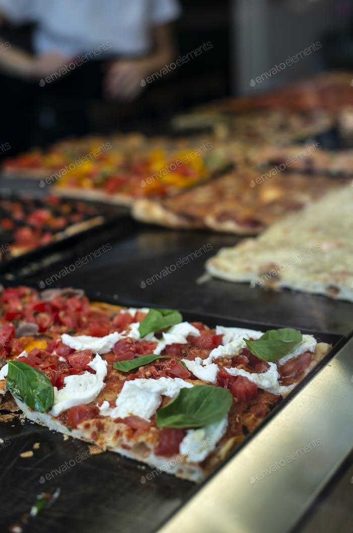Italian street pizza shop. Pizzas on showcase.