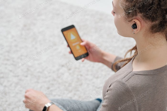 Young active woman with airpods holding smartphone while sitting on the floor