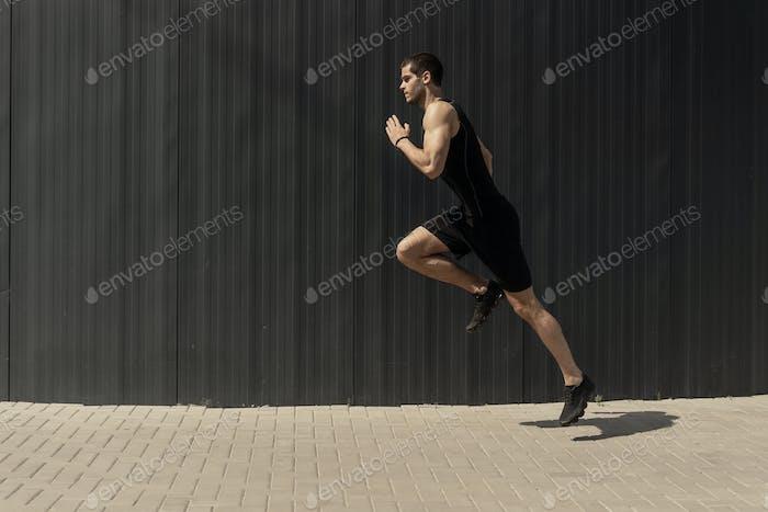 Eine Seitenansicht Aufnahme eines fit jungen, athletischen Mann springen und laufen.