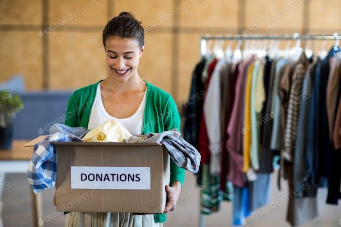 Mujer joven con caja de donación