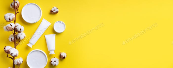 Fluffy cotton flowers, face cream, body butter on yellow background with copy space. Cosmetics