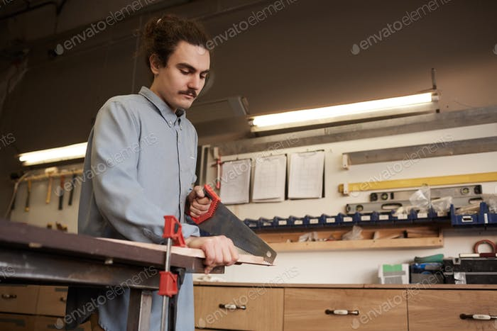 Man sawing the board with saw