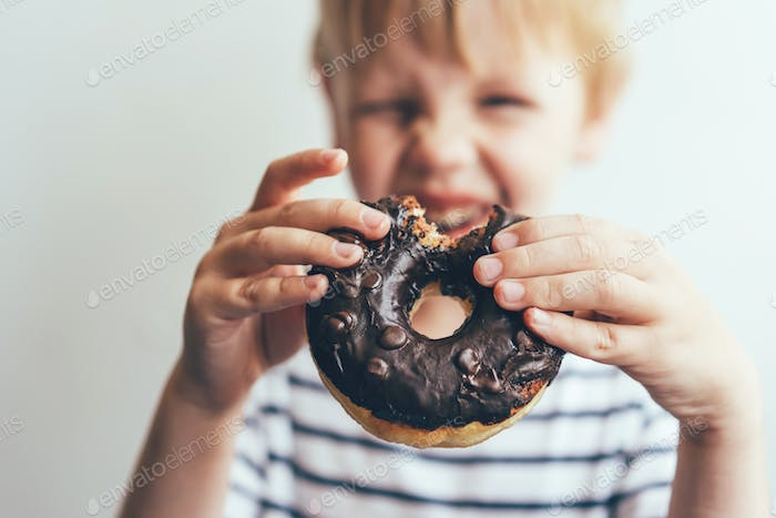 Closeup of a bitten chocolate donut in the hands of a child