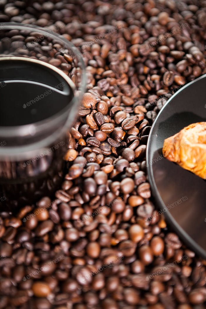 Croissant and coffee beans in close up