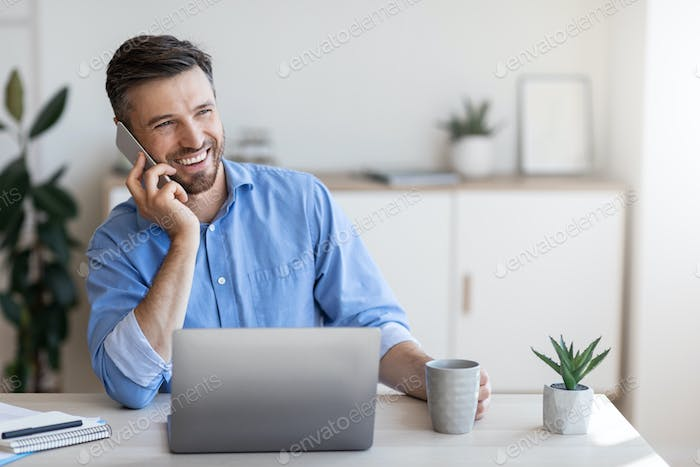 Smiling Male Office Employee Talking On Cellphone And Drinking Coffee At Workplace