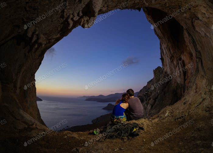 Romantic couple of rock climbers watching sunset