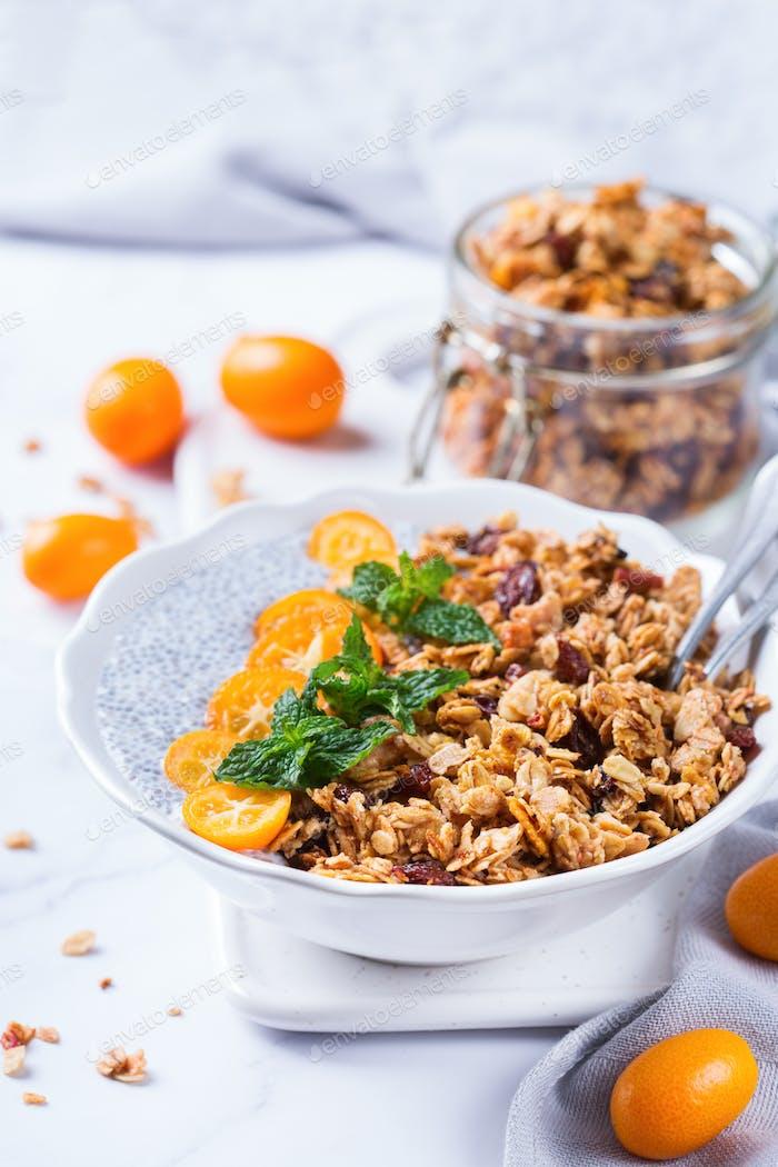 Chia Pudding Schüssel mit hausgemachtem Müsli und Kumquats zum Frühstück