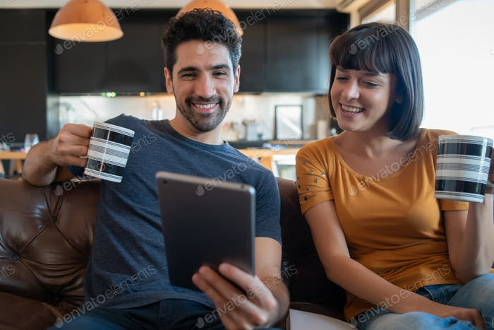 Couple on a video call with digital tablet at home.