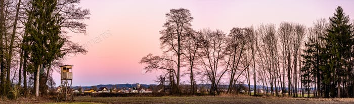 Panorama landscape with hunting tower after sunset in rural scenery against pink sky. Deer stand