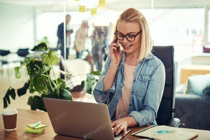 Smiling young businesswoman talking on a cellphone at her desk
