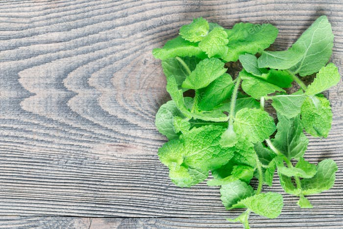 Fresh mint leaves on wooden table, horizontal, top view, copy sp