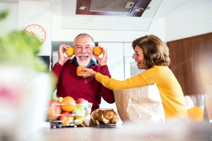 Senior couple unpacking food in the kitchen, having fun.
