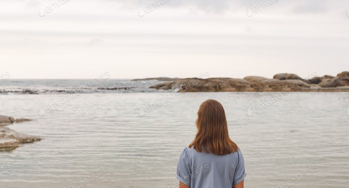 Rear view of young Caucasian woman standing at beach. She is looking the sea
