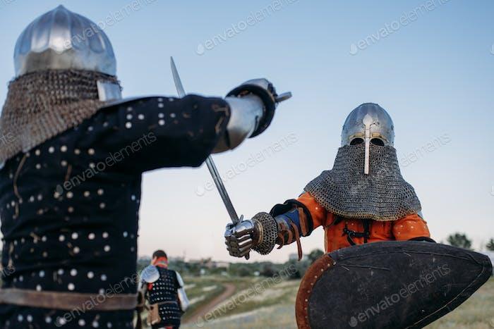 Caballeros con armadura y cascos pelean con espadas