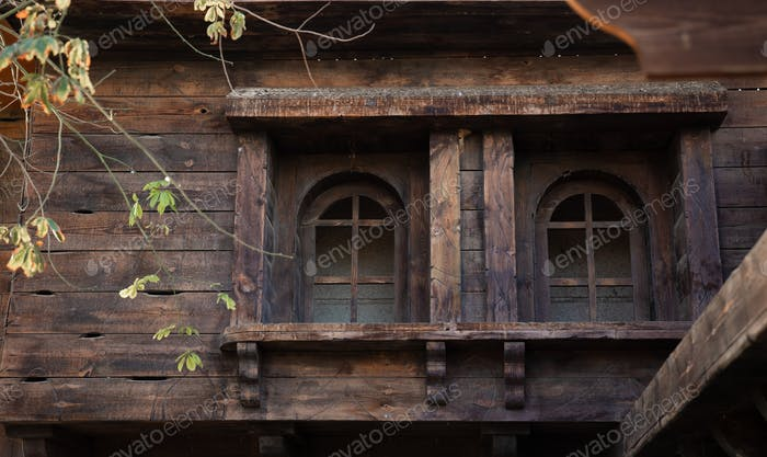 Old wooden house with wooden windows and shutters.