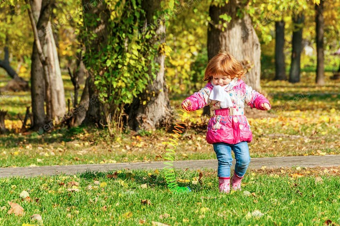 Girl playing in the park with a Rainbow spiral spring