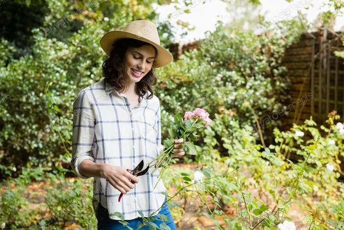 Woman trimming flowers with pruning shears in garden