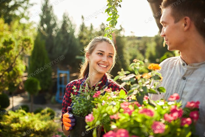Gärtner glücklich Junge und Mädchen halten Töpfe mit Pflanzen in schönen Gärten an einem warmen sonnigen Tag