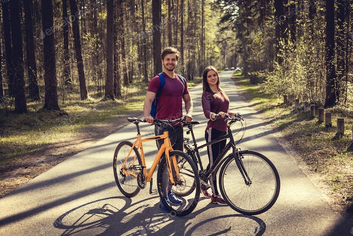 Sporty male and female with bicycles.