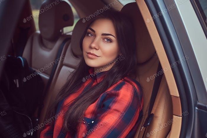 Портрет кавказской женщины в фланелевой рубашке, сидящей в