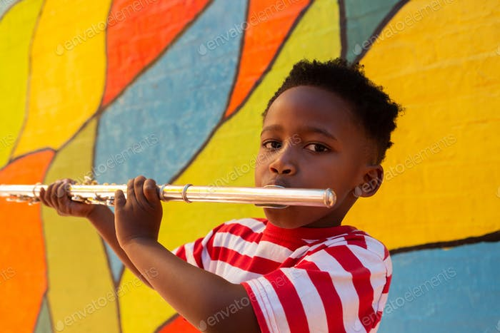 Portrait of African American schoolboy playing flute instrument in the school playground