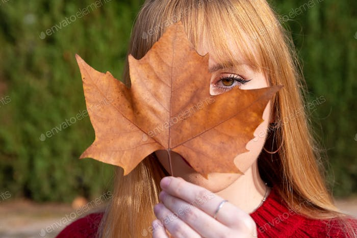 Blonde girl with painted lips and red sweater covering one eye with a tree leaf.