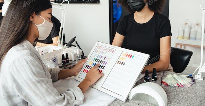 Neue Maniküre nach Lockdown und Wahl der modernen Farbe nach der Quarantäne. Asiatische Frau wählt Nagel