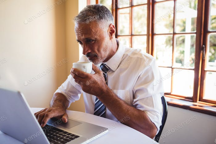 Businessman using laptop while having coffee