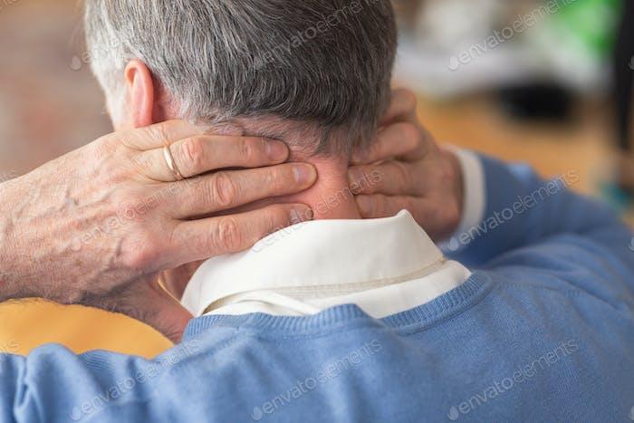 Elderly Man Having Neck Pain Sitting On Sofa, Rear View