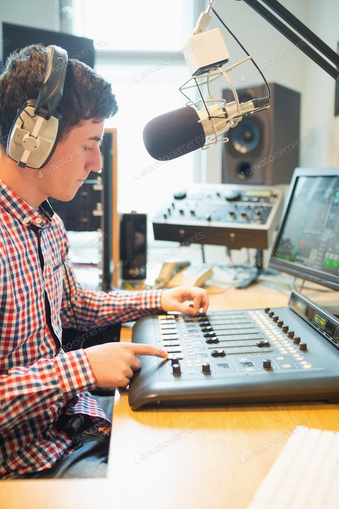 Radio host wearing headphones operating sound mixer on table in studio