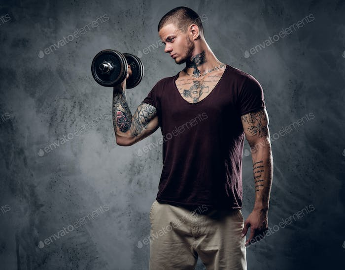 A man holds dumbbell over grey background.