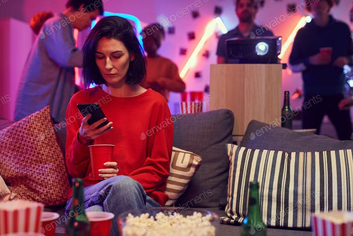 Woman using phone at party